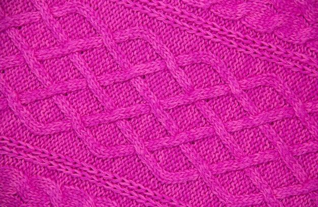 Trama a maglia di filato di lana rosa. motivo a trecce lavorato a mano a 12 punti. orizzontale. avvicinamento