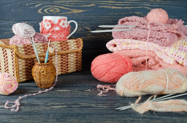Filato rosa e oggetti artigianali su un tavolo di legno