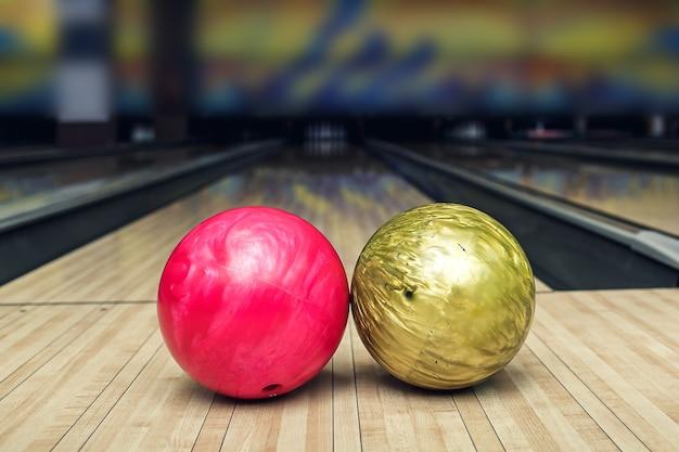 Palla rosa e gialla sulla pista da bowling prima del colpo.