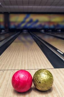 Palla rosa e gialla sulla pista da bowling prima del colpo