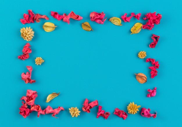 Cornice di bordo rettangolare di piante da fiore essiccate rosa e gialle su sfondo blu vista dall'alto laici piatta