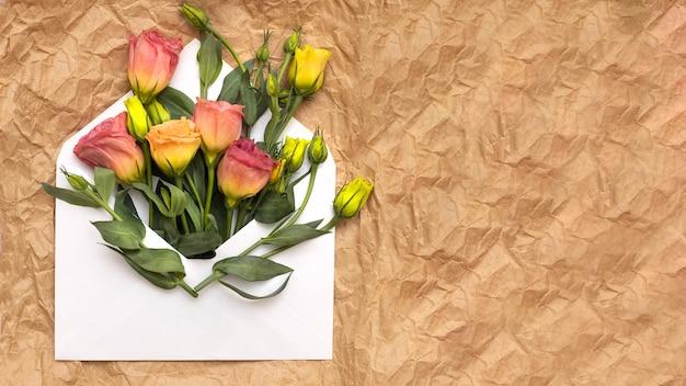 I fiori di eustoma rosa e gialli giacciono in una busta bianca aperta su uno sfondo di carta da pacchi spiegazzata.