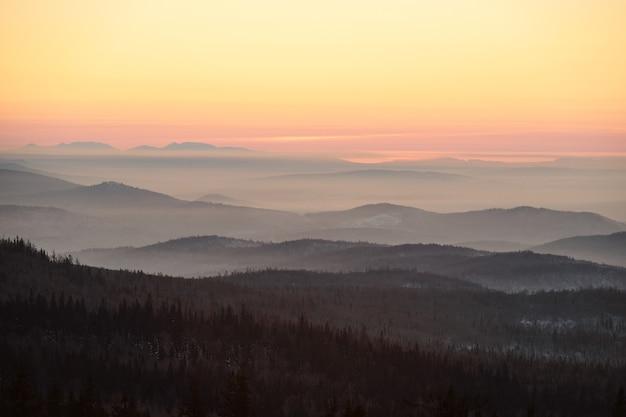 Cielo rosa e giallo e montagne ricoperte di foresta