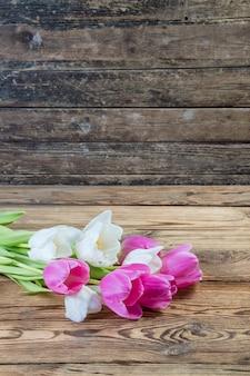 Fiori di tulipano rosa e giallo su fondo di legno rustico