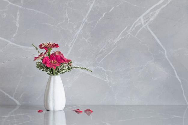 Fiori di zinnia rosa su vaso su fondo di marmo