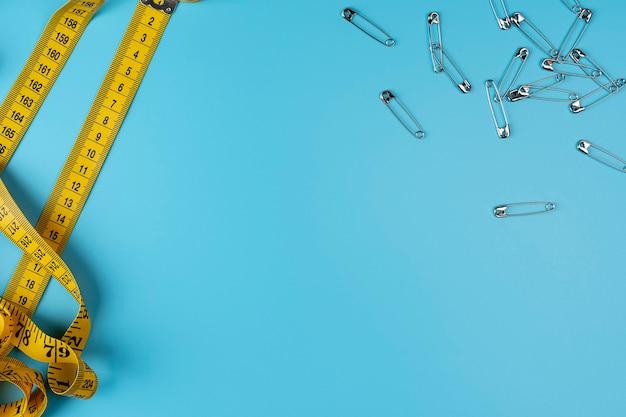 Spille e metro a nastro su misura con indicatori a forma di centimetri. righello centimetro arrotolato giallo e spilli in metallo. artigianato e concetto di cucito. copia spazio