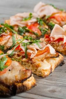 Pinsa romana tagliata a pezzi porzioni per una persona. pinsa con carne, rucola, formaggio.