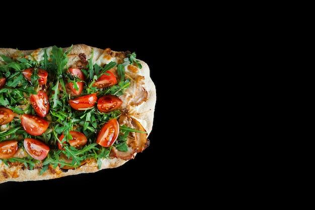 Pinsa romana gourmet cucina italiana su sfondo nero. scrocchiarella. pinsa con carne, rucola, pomodori, formaggio.