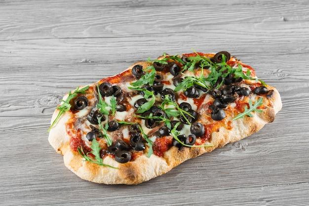 Pinsa romana gourmet cucina italiana sulla tavola di legno grigio. piatto tradizionale della scrocchiarella.