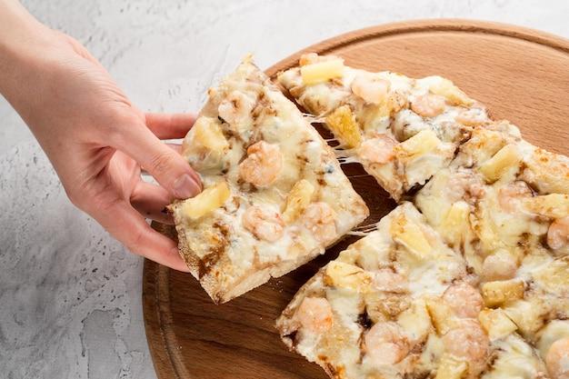 Pinsa romana con gamberi e ananas su piatto di legno su sfondo bianco. scrocchiarella di mare.
