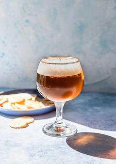 Pinta di birra chiara in bicchiere con patatine birra e snack