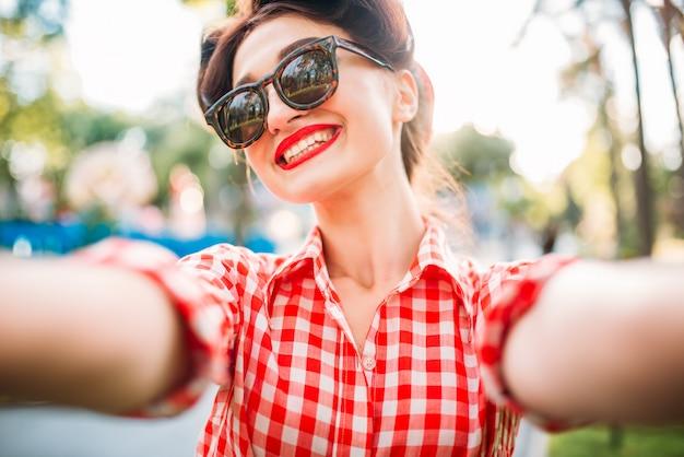Ragazza pinup in occhiali da sole, selfie girato all'aperto, moda americana degli anni cinquanta. modello attraente in stile pin up
