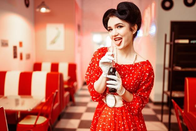 Ragazza pinup con trucco che beve bevanda gassata popolare in caffè retrò, 50 moda americana. abito rosso con pois, stile vintage