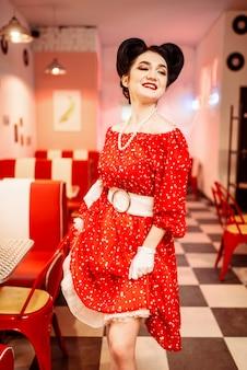 Pinup donna in abito rosso con pois bianchi, stile vintage. interiore del caffè retrò con pavimento a scacchiera