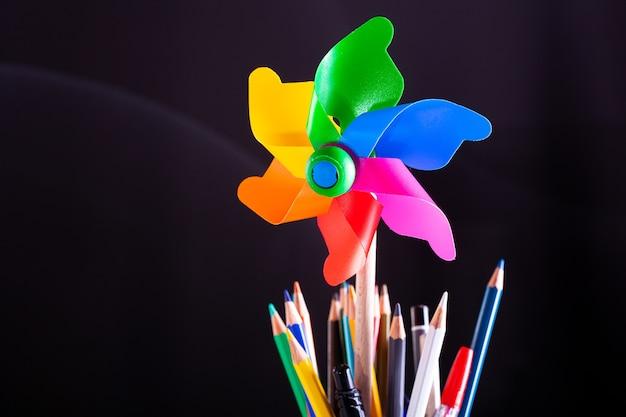 Girandola e matite pentola su libri impilati, forniture scolastiche sulla scrivania bianca con texture lavagna in background.. apprendimento, concetto di istruzione