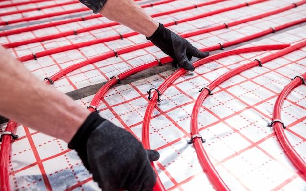 Pipefitter installa il sistema di riscaldamento a pavimento a casa
