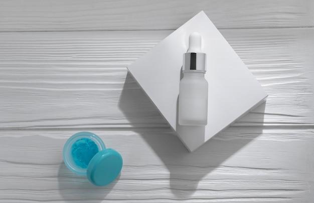 Bottiglia della pipetta sulla scatola bianca e gel blu aperto su fondo di legno bianco