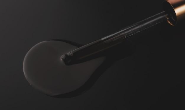 Pipetta e olio su sfondo nero