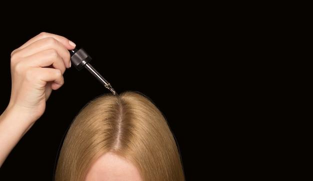 Pipetta con olio cosmetico per capelli e parte della testa