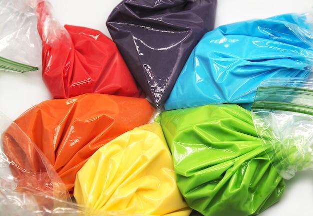 Sacchetti da pasticceria con glassa multicolore per la decorazione di torte o biscotti isolati su sfondo bianco