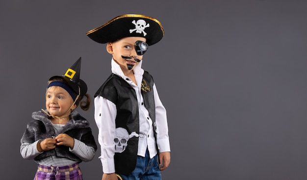 Ragazzo pirata e piccola strega per halloween. bambini in costumi di carnevale su un muro grigio con spazio laterale libero.