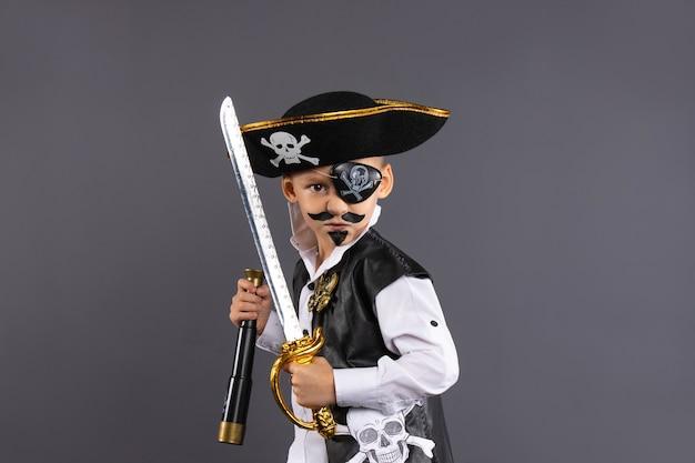 Capitano pirata con dipinto in una posa provocatoria. isolato su un muro grigio con abbondanza di spazio copia buon halloween.