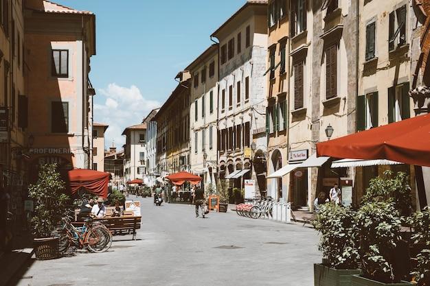 Pisa, italia - 29 giugno 2018: camminando su via borgo stretto nella città di pisa con edifici storici e negozi. la gente cammina e riposa. giornata di sole estivo e cielo blu