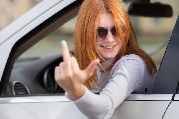 Donna aggressiva arrabbiata dispiaciuta incazzata alla guida di un'auto che grida a qualcuno con il gesto del dito medio.