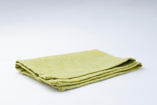 Tovagliolo di colore verde pista disposto su sfondo bianco a trama, isolato, fuoco selettivo.