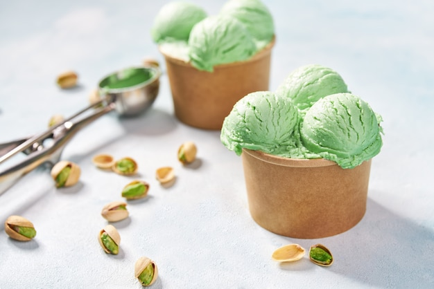 Il gelato al pistacchio in tazza di carta sulla menta colora il fondo, fuoco selettivo