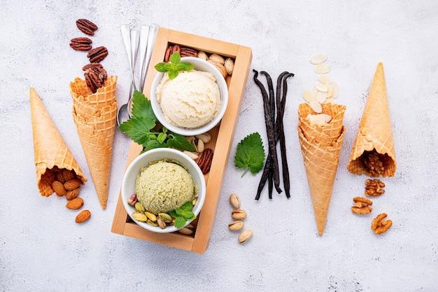 Gelato al pistacchio e alla vaniglia nella ciotola su priorità bassa di pietra bianca