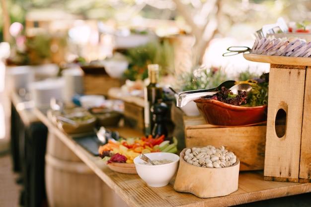 Pistacchi in una ciotola di legno su un tavolo con insalate su uno sfondo sfocato