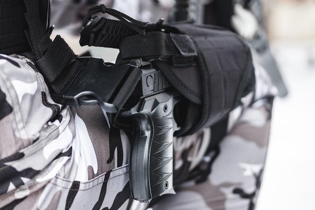 Una pistola in una fondina su un piede militare.