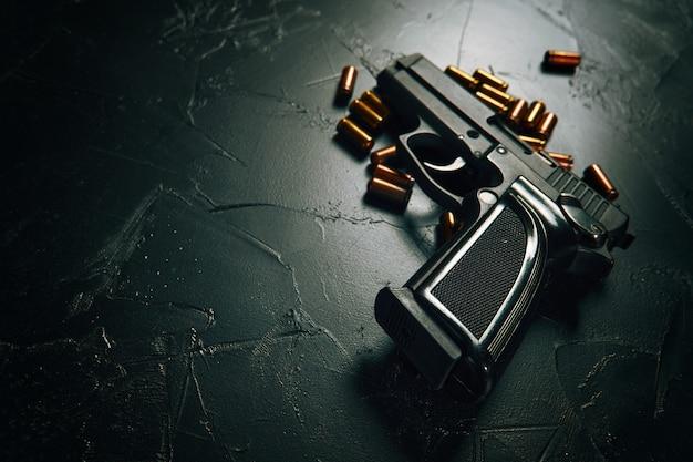 Pistola con proiettili sul tavolo di cemento pistola nera e cartucce d'ottone armi da fuoco armi da fuoco arma di crim...