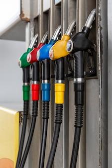 Pistole con diversi tipi di carburante alla stazione di servizio. verticale.