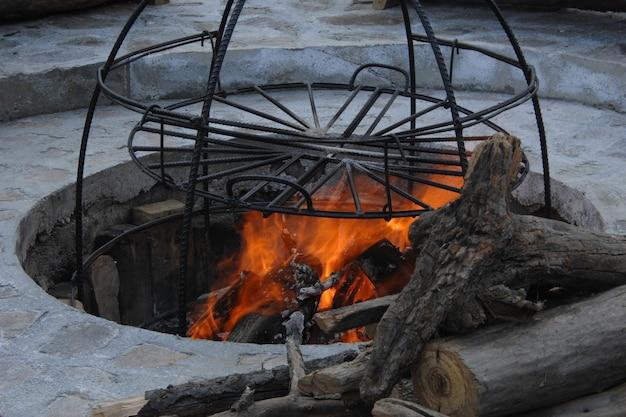 Nella fossa una costruzione di aste metalliche per il fumo. struttura in metallo per la cottura sul fuoco