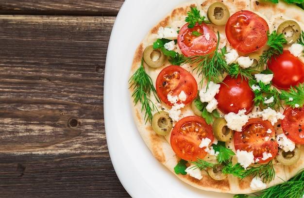 Pita con hummus, formaggio, pomodorini, olive e verde su fondo di legno rustico.