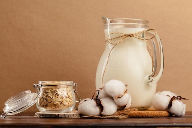 Brocca di latte fresco sulla tavola di legno contro il beige si chiuda