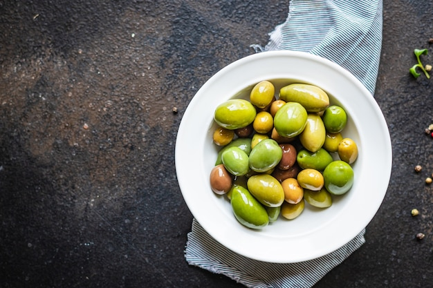 Olive snocciolate in un piatto sul tavolo diverse varietà di frutta vegana o vegetariana