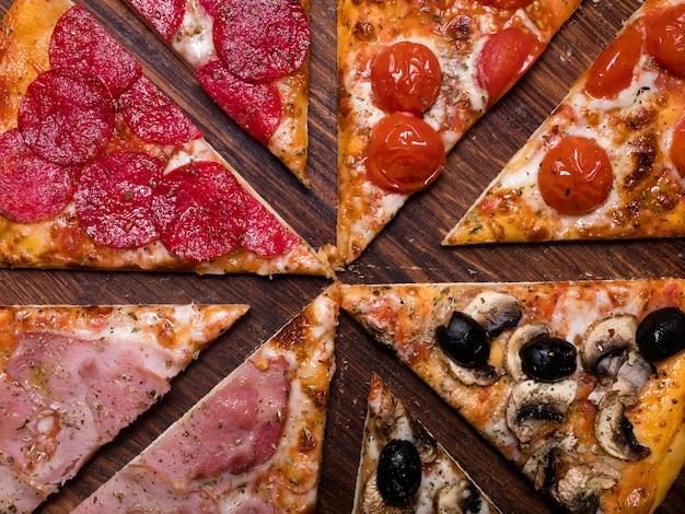 Sfondo di pizza. pasto alimentare nazionale italiano. quattro stagioni con prosciutto prosciutto pomodori olive e funghi topping