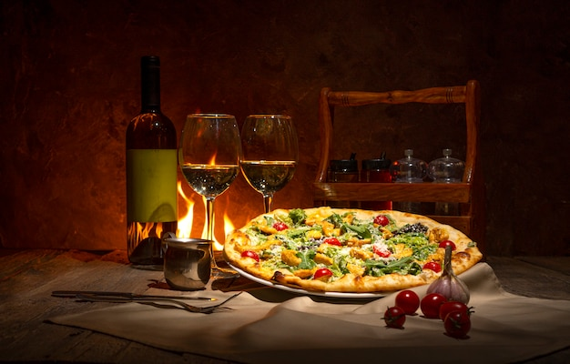 Pizza, bottiglia di vino bianco e due bicchieri di vino contro il camino. atmosfera romantica serale nel ristorante italiano.