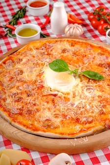 Pizza carbonara con pancetta, uovo, parmigiano, basilico fresco e salsa di pomodori su una tavola di legno