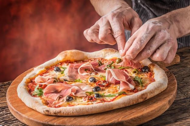 Pizza e chef. lo chef del ristorante prepara una pizza e la decora con prosciutto