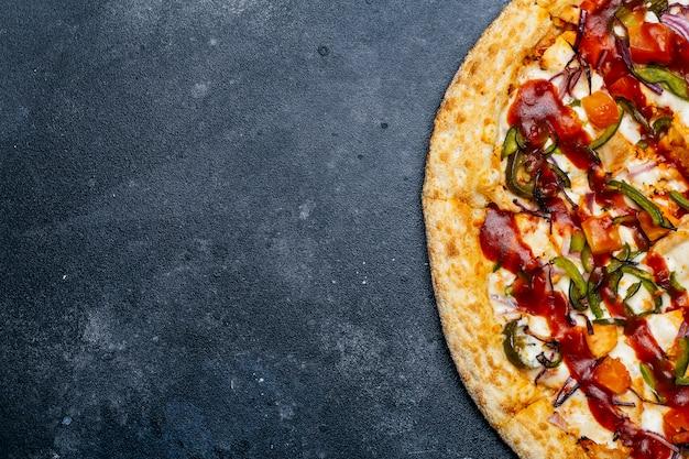 Pizza su uno sfondo scuro. classica pizza italiana con pomodoro, pepe, verdure, salsa e formaggio mazarella su un tavolo da cucina scuro. copia spazio