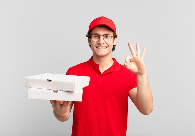 La pizza consegna il ragazzo sentendosi felice, rilassato e soddisfatto, mostrando approvazione con un gesto ok, sorridendo