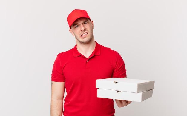 La pizza consegna l'uomo che si sente perplesso e confuso, con un'espressione stupida e sbalordita che guarda qualcosa di inaspettato