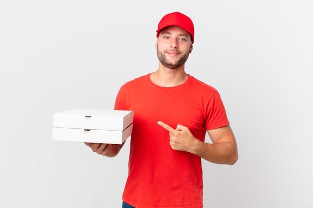 La pizza consegna l'uomo che sorride allegramente, si sente felice e indica il lato