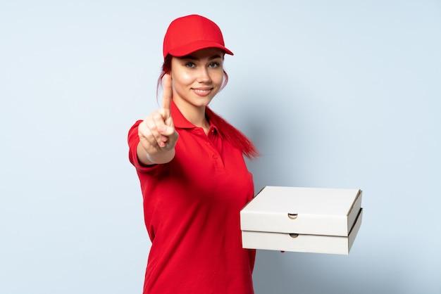 Ragazza di consegna della pizza che tiene una pizza sopra fondo isolato che mostra e che solleva un dito