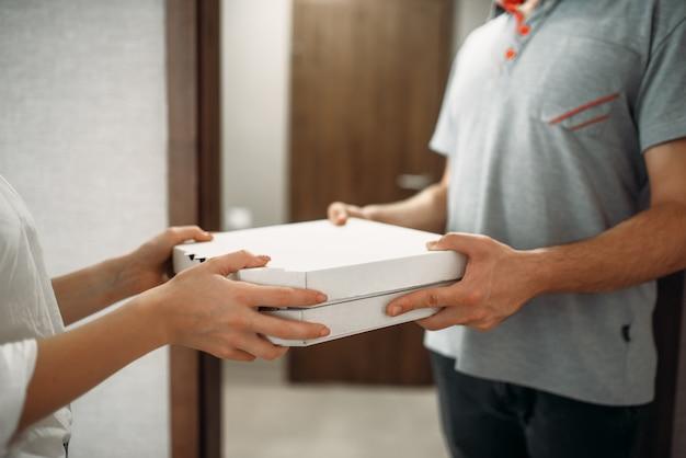 Il fattorino della pizza dà la scatola di cartone al cliente femminile alla porta