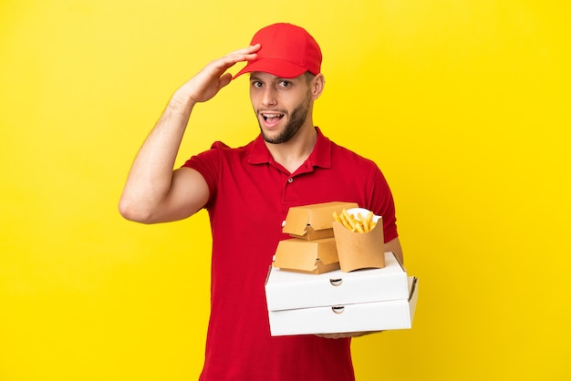 Pizza consegna uomo di prelevare scatole per pizza e hamburger su sfondo isolato facendo un gesto a sorpresa mentre si guarda al lato